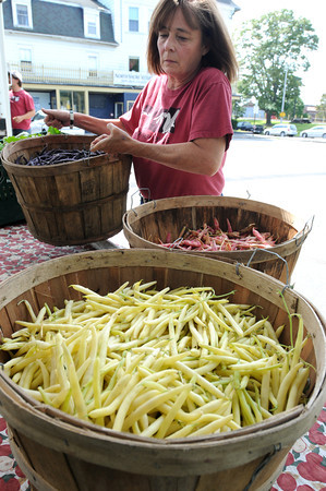 Beverly:<br /> Karen Albee readies baskets of vegetables at Farmer Dave's booth before the start of Beverly Farmers' Market.<br /> Photo by Ken Yuszkus/The Salem News, Monday, August 20, 2012.