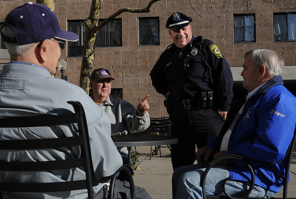 Peabody:<br /> Bob Mahoney, Peabody police officer, speaks with seated residents of the Peabody House, in front of the Peabody House, from left, Emile Morin, Duke Girard, and Roger Moreneau. Not shown in the photo is Armand Gagne. The Peabody House is one area patroled by officer Bob Mahoney.<br /> Photo by Ken Yuszkus/Salem News, Wednesday November 18, 2009.