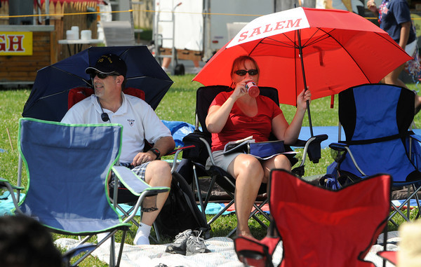 Salem:<br /> Richard and Therese Eisner of Salem are under umbrellas, protected from the sun while listening to the music at the Fourth of July activities at the Salem Maritime Site.<br /> Photo by Ken Yuszkus/Salem News, Wednesday, July 4,  2012.
