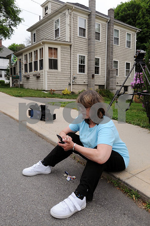 Ipswich:<br /> Gloria Droukis, a neighbor, texts the owners of the house at 15 Putnam Street where a child fell from the second story window. 15 Putnam Street is in the background.<br /> Photo by Ken Yuszkus/Salem News,  Wednesday, June 3, 2009.