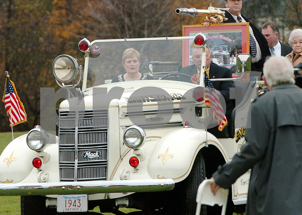 Danvers:<br /> Jewel Barnett, widow of Donald Barnett, Jr.,  sits in the passenger seat of an antique fire truck that Donald's friend, Ron Skinner, is driving onto the field at Plains Park at the start of the memorial service for Donald Barnett, Jr.. Donald's remains are carried by Jewel in the truck.<br /> Photo by Ken Yuszkus/Salem News, Friday, November 7, 2008.