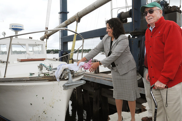 Salem:<br /> Thomas G. Brown, Jr., right, of Gloucester, donated his 34' Webber Cove power boat to Sail Salem. Salem Mayor Kim Driscoll christens the boat with a bottle of champagne at Dion Yatch Yard.<br /> Photo by Ken Yuszkus/Salem News, Tuesday, August 16, 2011.
