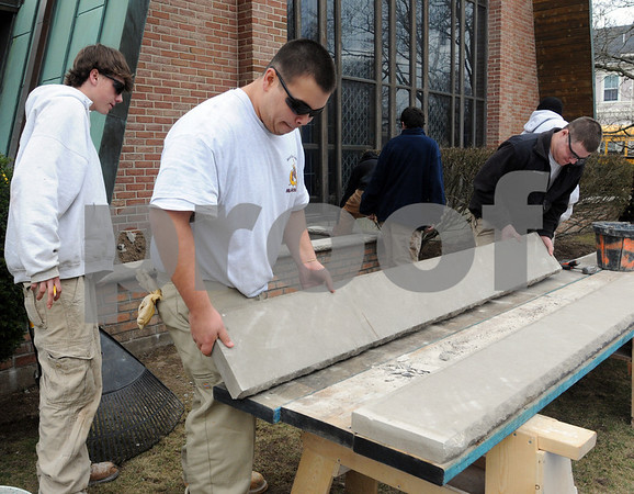 Danvers:<br /> From left, Shane Bennett of Danvers, watches  Brendan Lopez of Salem, and Paul Cerino of Gloucester, ready building materials to trimmed. North Shore Technical High masonry students are rebuilding two brick planters at the front of Holy Trinity Methodist Church.  The church bought the bricks and supplies and six students supply the free labor.<br /> Photo by Ken Yuszkus/Salem News, Monday, April 6, 2009.