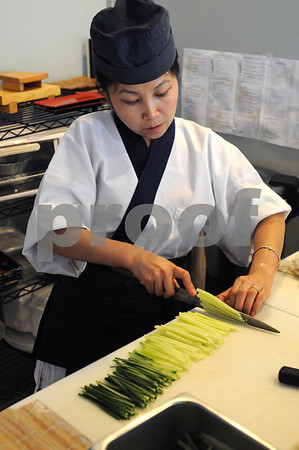 Salem:<br /> Fawn Lei Sandler cuts up a cucumber at the sushi bar. She recently opened Okea Grill and Sushi. Being a female sushi chef is rare in the male-dominated profession. <br /> Photo by Ken Yuszkus/Salem News, Wednesday, June 24, 2009.