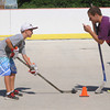 Marblehead:<br /> Charlie McGurrin, 8, left, is coached by Max Delvento of the Marblehead High varsity hockey team at the Dry Land Hockey Training camp in Marblehead for boys and girls in grades 2-8 held at the Bud Orne Memorial Rink. They were assisted by coaches as well as members of the Marblehead High varsity hockey team.<br /> Photo by Ken Yuszkus/Salem News, Tuesday, August 7,  2012.