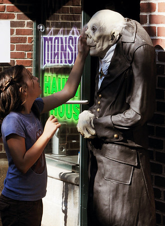 Salem:<br /> Adelia Sand, of Salem, touches a statue outside one of the businesses on Essex Street on Sunday during the Salem Haunted Happenings.<br /> Photo by Ken Yuszkus/Salem News, Monday, October 10, 2011.