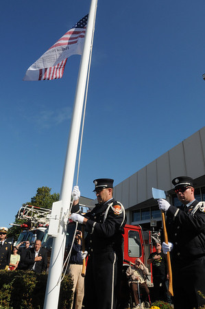 Danvers:<br /> Lt. Jim Brooks, Danvers firefighter, lowers the flag to half mast during the 9/11 ceremony in front of the Danvers Fire Department Sunday morning. <br /> Photo by Ken Yuszkus/Salem News, Sunday, September 11, 2011.