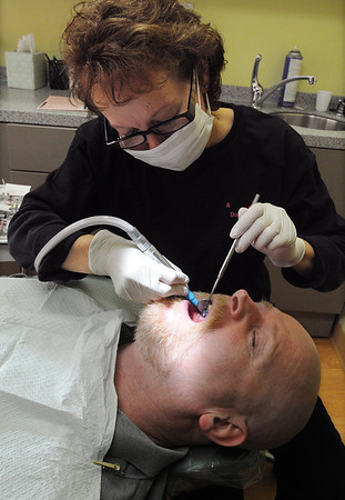 Peabody:<br /> Sharon Coleman, dental hygenist, works on Barry Swift during the fifth annual Dentistry With A Heart campaign held at Varinos Dental Associates in Peabody on Friday.<br /> Photo by Ken Yuszkus/Salem News, Friday, February 10, 2012.