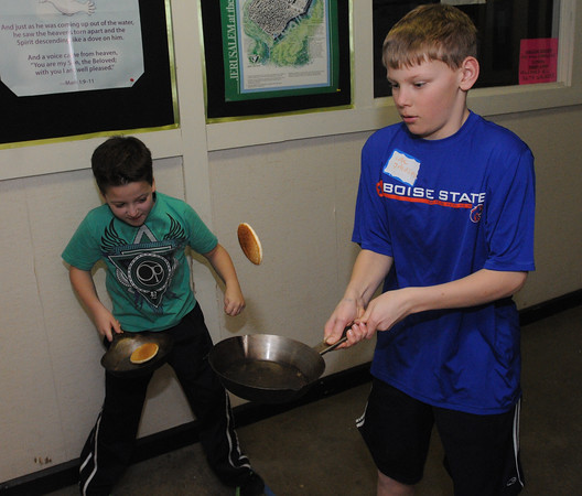 Danvers:<br /> Zachary Costa, left, and Cole Johnson flip their pancakes from a frying pan at a designated line as part of the relay race during the Shrove Tuesday Pancake Dinner at the Maple Street Church Tuesday evening in Danvers.<br /> Photo by Ken Yuszkus/Salem News, Tuesday March 8, 2011.