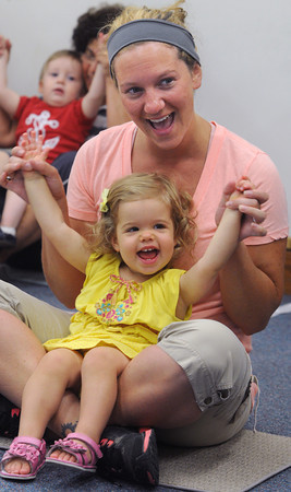 Salem:<br /> Madiline Costa, 17 months old, along with her nannie, Ashley Bostrom, participate in the Play With Me program at the Salem Public Library. The Wednesday morning program consisted of songs, fingerplays, lap games, and stories for babies, ages 0 to 24 months.<br /> Photo by Ken Yuszkus/Salem News, Wednesday, July 18,  2012.