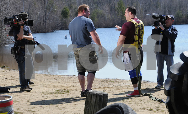 Wenham:<br /> David Hansen, left center, and Rob Meulenberg, right center, talk about the details of each running with a bungee cord attached to see how far they can travel with the resistance from the cord as a cameraman film their attempt. The Discovery Channel film crew were filming at Gull Pond at Gordon College.<br /> Photo by Ken Yuszkus/Salem News, Friday, April 17, 2009.