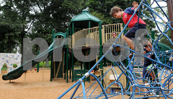Salem:<br /> Calder Gebhardt, left, and Cole Lamoureaux climb on the new playground equipment at Forest River Park.<br /> Photo by Ken Yuszkus/Salem News, Wednesday, August 12, 2009.