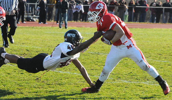 Topsfield:<br /> Masco's Mike Tivinis gets pulled down by North Andover's Ahamdi Ogwuru at the North Andover at Masconomet football game on Thanksgiving Day.<br /> Photo by Ken Yuszkus/Salem News, Thursday, November 24, 2011.