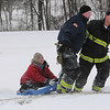 Beverly:<br /> Firefighters Bob Atherton, Derek Belanger, and Peter Davis, bring one of the two girls rescued from a pond at the Beverly Golf and Tennis Club on a sled to the ambulance Monday afternoon.<br /> Photo by Ken Yuszkus/Salem,  News, Monday,  December 27, 2010.