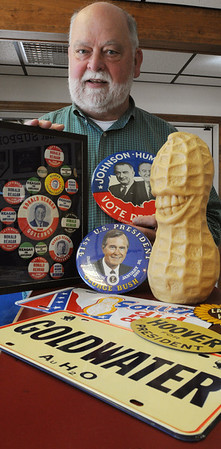 Danvers:<br /> Alan Hartnett is well known as a local car wash owner, but he's also an avid collector of political memorabilia. He is holding Ronald Reagan buttons and a large Johnson-Humphrey button. In front of him is a George Bush button, a peanut statue and license plate made for the Jimmy Carter campaign, a Barry Goldwater license plate, and a Herbert Hoover metal sign.<br /> Photo by Ken Yuszkus/Salem News, Wednesday, February 8, 2012.