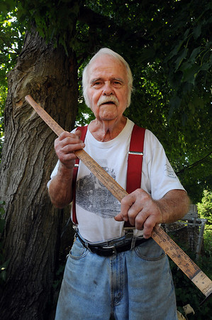 Wenham:<br /> Harold Boothroyd, is retiring after 40 years as the Wenham's lumber surveyor and measurer of tree and bark. He is holding a tally rod while standing near a large maple tree in his backyard. Although he never used one for the job, the tally rod was used to measure around the trunk of a tree.<br /> Photo by Ken Yuszkus/Salem News,Thursday, July 8, 2010.