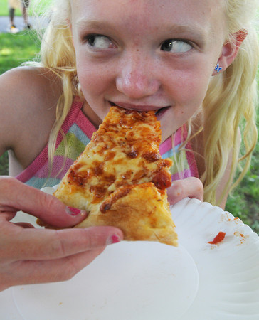 Salem:<br /> Mikayla Bushong of Salem, bites into a slice of pizza during Salem's Best Pizza Competition at the Salem Common Monday night.<br /> Photo by Ken Yuszkus/Salem News, Monday, August 6,  2012.