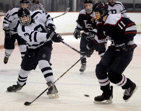Peabody:<br /> Peabody's Derek Demild, left, shoots the puck at the goal during the Lincoln-Sudbury at Peabody boys hockey game at the McVann-O'Keefe Rink.<br /> Photo by Ken Yuszkus/Salem News, Monday, January 16, 2012.