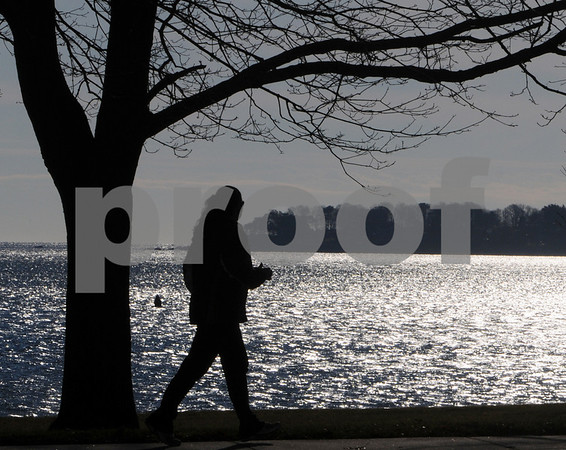 Beverly:<br /> A morning jogger runs on Lothrop Street past Lyons Park as the sunshine sparkles on Salem Harbor in the background. <br /> Photo by Ken Yuszkus/Salem News, Tuesday December 2, 2008.