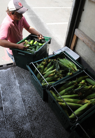 Beverly:<br /> Victor Catelli from Farmer Dave's removes a crate of cucumbers from the truck to set up for Beverly Farmers' Market.<br /> Photo by Ken Yuszkus/The Salem News, Monday, August 20, 2012.