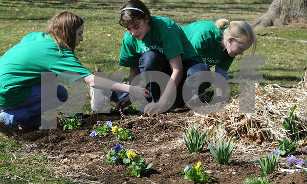 Beverly:<br /> From left, Sophia Martin, Jessica Wahl, and Izzy Dow, plant panzies in front of the Briscoe Middle School. The Build a Better Briscoe Club and volunteers focused on cleaning up the grounds, weeding, replanting the barrel plantings, planting flowers and assisting in recycling.<br /> Photo by Ken Yuszkus/Salem News, Wednesday, April 15, 2009.