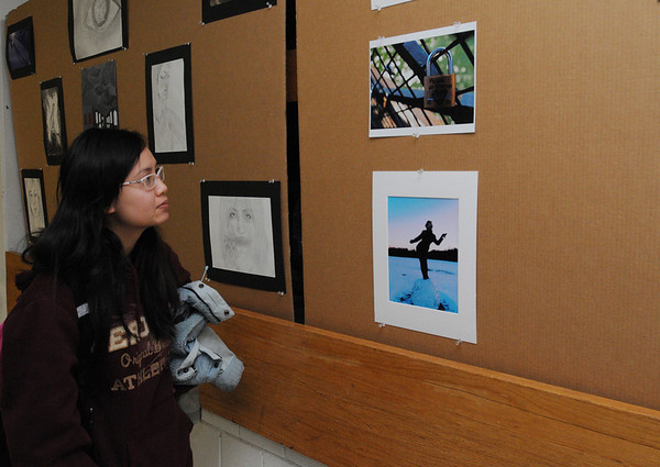 Salem:<br /> Susan Le, a senior, looks over the art on the hallway wall during the Salem High School annual Deck The Halls Art Exhibit at the shool. Students showcased their photography, graphic design, drawing, painting, sculpture, tv production/digital media, and woodworking.<br /> Photo by Ken Yuszkus/Salem,  News, Wednesday,  December 22, 2010.