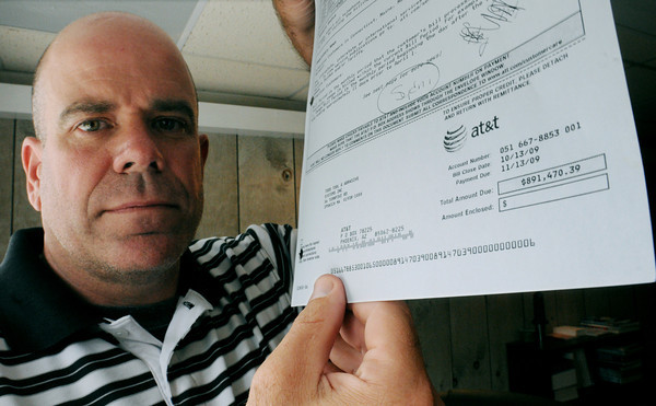 Ipswich:<br /> Michael Smith, president of Todd Tool, holds a bill from AT&T for $891,470.39 which was billed to his company.<br /> Photo by Ken Yuszkus/Salem News, Thursday, July 5,  2012.