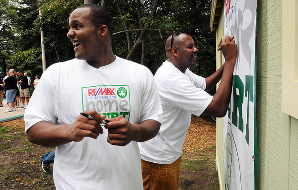 """Salem:<br /> Celtics Glen """"Big Baby"""" Davis, left, and former Celtics Cedric Maxwell, sign a banner while at the Plummer Home for Boys for the dedication of the basketball court that the Celtics helped build along with the NFL quarterback Steve Young's Foundation. They also shot a few hoops with the kids.<br /> Photo by Ken Yuszkus/Salem News, Monday August 16, 2010."""