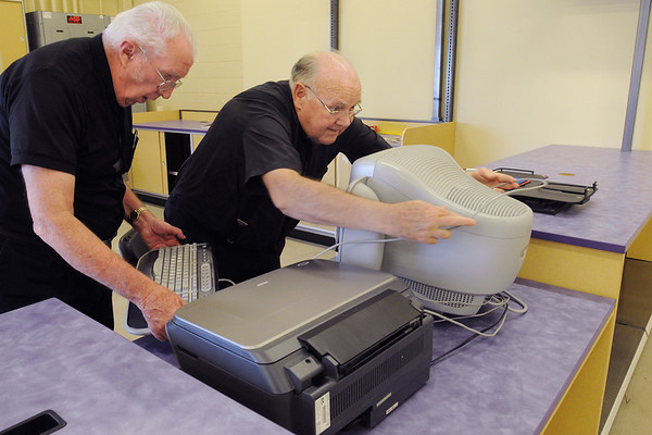 Peabody:<br /> Father Felix Prior, left, and Father Herbert Jones install a computer at the new location for the Carmelite Chapel. While the mall chapel is being renovated, the chapel has been moved to the old Office Depot.<br /> Photo by Ken Yuszkus/Salem News, Thursday, April 8, 2010.