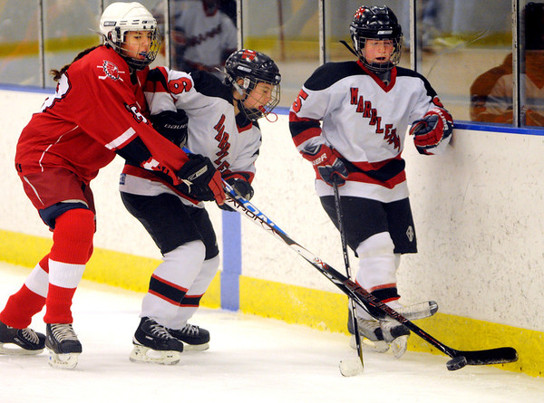 Salem:<br /> From left, Masconomet's Becca Cleary, Marblehead's Caroline Hughes, and Meg Gray battle for the puck along the boards during the Marblehead vs. Masconomet girls hockey at Salem State's hockey rink.<br /> Photo by Ken Yuszkus/Salem News, Tuesday, December 27, 2011.