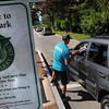 Beverly:<br /> Scott Blanchette, Lynch Park gate attendant, checks the car registration for residency at the entrance at Lynch Park. A Carry In Carry Out sign is at the entrance. The signs are posted at various spots in Lynch Park.<br /> Photo by Ken Yuszkus/Salem News, Friday, July 15, 2011.