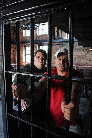 Salem:<br /> Shane Andruskiewicz, general manager, left, and Cleber Santos, owner, of the Great Escape restaurant, stand behind some of the original jail bars at the restaurant. The restaurant will be opening soon.<br /> Photo by Ken Yuszkus/Salem News, Friday,  August 20, 2010.