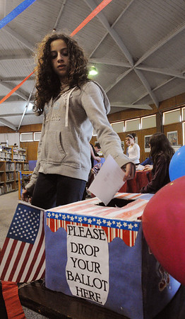 Peabody:<br /> Maya Shapiro, 7th grade student at Higgins Middle School, places her ballot in the ballot box during the school's primary on Monday.<br /> Photo by Ken Yuszkus/Salem News, Monday,  March 5, 2012.