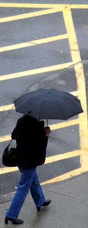 Salem:<br /> A pedestrian with an umbrella walks on Church Street during the heavy rain that drenched the area on Tuesday.<br /> Photo by Ken Yuszkus/Salem News, Tuesday, March 30, 2010.