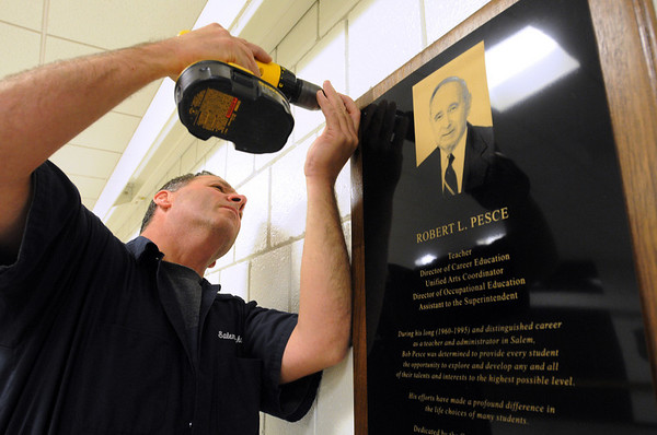 Salem:<br /> Torin Mailloux, maintainence foreman at Salem High School hangs the plaque in the Unified Arts wing which was dedicated to Bob Pesce at Salem High School on Saturday.  <br /> Photo by Ken Yuszkus/Salem News, Saturday,  November 6, 2010.