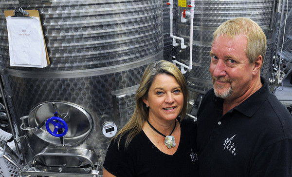 Rowley:<br /> Donna Martin and Rick Rouseau of the Mill River Winery stand in front of some of their large stainless steel tanks used to ferment wine.<br /> Photo by Ken Yuszkus/Salem News, Friday, July 20,  2012.