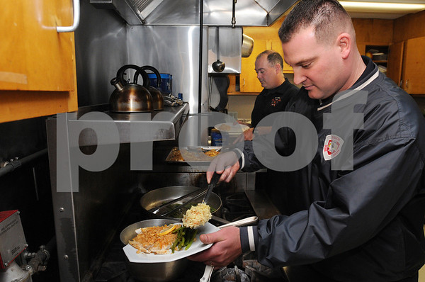 Salem:<br /> Salem firefighter Paul Michaud, right, places a portion of rice pilaf onto his plate as firefighter Pat Burke reaches for a piece of haddock. Pat Burke prepared lunch for the crew at the Salem Fire Department.<br /> Photo by Ken Yuszkus/Salem News, Monday December 8, 2008.