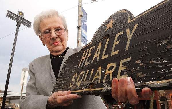 Beverly:<br /> Lois Healey is the widow of Frederick Healey, a veteran for whom Healey Square was named in 1976. On Veterans Day this year the city mistakenly rededicated the square in honor of another veteran, Joseph Healey. The city has ackowledged its mistake and plans to put up a new sign in honor of Frederick Healey. Mrs. Healey is holding the old Healey Square sign in honor of her husband. The newer Joseph Healey sign is to the left of Lois Healey.<br /> Photo by Ken Yuszkus/Salem News, Monday, November 28, 2011.