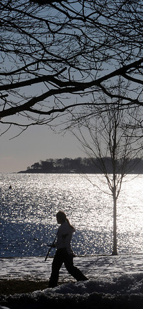 Beverly:<br /> A walker passes through the reflections of the sun off the ocean at Danes Street Beach on a sunny morning.<br /> Photo by Ken Yuszkus/Salem News, Monday, January 3, 2011.