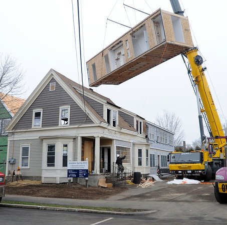 Danvers:<br /> A prefabricated building section is lifted into the air by a crane to be put in place at 74 Elm Street.<br /> Photo by Ken Yuszkus/Salem News, Wednesday,  March 14, 2012.
