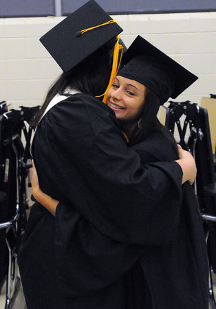 Ipswich:<br /> Paige DeMarco, left, and Brianna Maglio hug as they greet each other before the start of the Ipswich High School graduation.<br /> Photo by Ken Yuszkus/Salem News, Sunday, June 3, 2012.