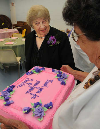 """Hamilton:<br /> Mary Maione, left, looks over the cake which thanks her for years of service was displayed by Mimi Fanning, chairman of the Council on Aging. Mary Maione, a longtime volunteer with Hamilton's Council on Aging, is retiring as a member of the Hamilton Council on Aging's board of directors.  Selectmen have declared Monday as """"Mary Maione Day"""" at a reception held in her honor.<br /> Photo by Ken Yuszkus/The Salem News, Monday, September 5, 2012."""