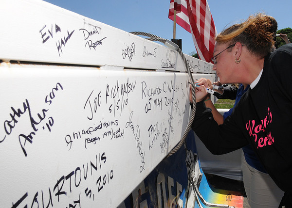 Danvers:<br /> Student Vicki Nickerson signs her name on the final beam just before it was placed on the New Zero Net energy building at NSCC.<br /> Photo by Ken Yuszkus/Salem News, Tuesday, May 5, 2010.