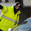 Salem:<br /> Sergeant Marc Berube gives directions to a motorist while at his work detail on Bridge Street. Sergeant Marc Berube wears protective clothing to shield him from the strong frigid wind that hit the area Friday. <br /> Photo by Ken Yuszkus/Salem News, Friday, January 29, 2010.