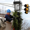 Peabody:<br /> Nelson Burke, of the Peabody Fire Department, hangs a wreath on a lamp post on Central Street.<br /> Photo by Ken Yuszkus/Salem News, Tuesday, November 29, 2011.