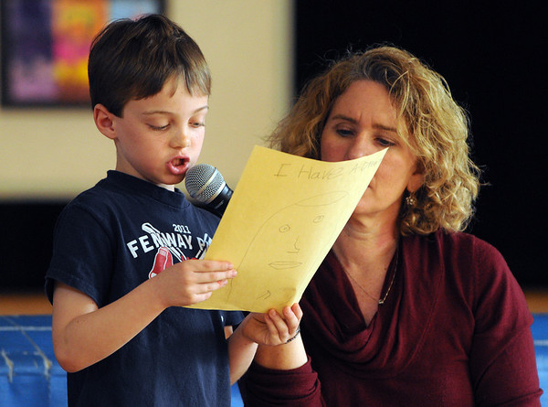 "Wenham:<br /> Tate Fitzgibbons, first-grader at the Buker Elementary speaks about note taking. Kathy O'Shea, first-grade teacher, helps him while he talks about one particular book in front of the school audience as part of the ""Read Across America"" program Friday morning.<br /> Photo by Ken Yuszkus/Salem News, Friday,  March 9, 2012."