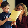 """Wenham:<br /> Tate Fitzgibbons, first-grader at the Buker Elementary speaks about note taking. Kathy O'Shea, first-grade teacher, helps him while he talks about one particular book in front of the school audience as part of the """"Read Across America"""" program Friday morning.<br /> Photo by Ken Yuszkus/Salem News, Friday,  March 9, 2012."""