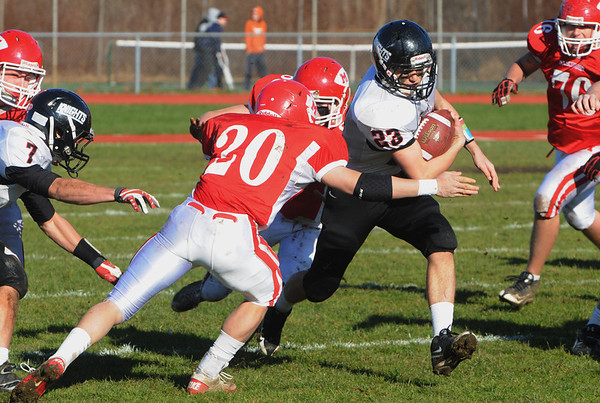 Topsfield:<br /> North Andover's John Lannone runs through a hole as Masco's Dylan Mann closes in at the North Andover at Masconomet football game on Thanksgiving Day.<br /> Photo by Ken Yuszkus/Salem News, Thursday, November 24, 2011.