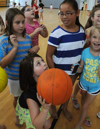 Danvers:<br /> Bella Gillis, 7, aims before shooting for a basket during free time at the Holten Richmond Middle School gym. Basketball was the game of the day at the Hip Hop Girls Club.<br /> Photo by Ken Yuszkus/Salem News, Thursday, July 19,  2012.