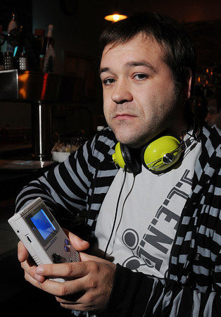 "Salem:<br /> Scott Buchanan, a dj and ""chip tune"" musician, who uses hand-held gameboys and video game systems to make music. He is holding a gameboy.<br />  Photo by Ken Yuszkus/Salem News, Monday November 30, 2009."